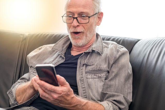 Senior s mobilním telefonem (ilustrační foto)