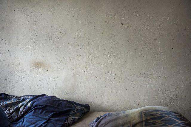 Fleky na zdi po mrtvých štěnicích, postel pana Vlastimila z Modré ubytovny.